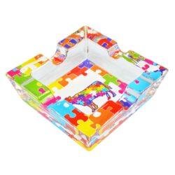 Cigaretový popelník skleněný Puzzle-Cigaretový popelník skleněný Puzzle. Hranatý popelník na cigarety se čtyřmi odkládacími místy je vyrobený ze silného skla. Díky větší šířce dvou odkládacích míst, je tento popelník vhodný také pro doutníky. Tloušťka stěny je 1,4cm. Dno popelníku je potištěné atraktivním barevným motivem. Rozměry popelníku: 10x10x3,1cm. Popelník je dodávaný v kartonové krabičce.
