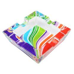 Cigaretový popelník skleněný Rainbow-Cigaretový popelník skleněný Rainbow. Hranatý popelník na cigarety se čtyřmi odkládacími místy je vyrobený ze silného skla. Díky větší šířce dvou odkládacích míst, je tento popelník vhodný také pro doutníky. Tloušťka stěny je 1,4cm. Dno popelníku je potištěné atraktivním barevným motivem. Rozměry popelníku: 10x10x3,1cm. Popelník je dodávaný v kartonové krabičce.