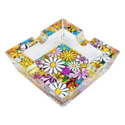 Cigaretový popelník skleněný Flowers-Cigaretový popelník skleněný Flowers. Hranatý popelník na cigarety se čtyřmi odkládacími místy je vyrobený ze silného skla. Díky větší šířce dvou odkládacích míst, je tento popelník vhodný také pro doutníky. Tloušťka stěny je 1,4cm. Dno popelníku je potištěné atraktivním barevným motivem. Rozměry popelníku: 10x10x3,1cm. Popelník je dodávaný v kartonové krabičce.