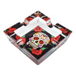 Cigaretový popelník skleněný Skull-Cigaretový popelník skleněný Skull. Hranatý popelník na cigarety se čtyřmi odkládacími místy je vyrobený ze silného skla. Díky větší šířce dvou odkládacích míst, je tento popelník vhodný také pro doutníky. Tloušťka stěny je 1,4cm. Dno popelníku je potištěné atraktivním barevným motivem. Rozměry popelníku: 10x10x3,1cm. Popelník je dodávaný v kartonové krabičce.