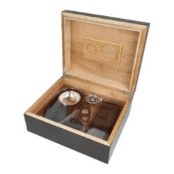 Humidor na doutníky SET 25, černý, 26x22,5x10,5cm-Stolní humidor na doutníky SET s kapacitou cca na 25 doutníků (v závislosti na velikosti). Praktická sada obsahující humidor a doutníkové příslušenství, které jistě ocení každý kuřák doutníků. Doutníkový set obsahuje mimo humidoru doutníkový popelník s kovovou vložkou, plastový doutníkový ořezávač v černém provedení a černé koženkové pouzdro na dva doutníky. Elegantní humidor je v černé barvě s pololesklým povrchem. Na vnitřní straně víka najdeme prostor pro uchycení vyměnitelného vlhkoměru a zvlhčovače s houbou, které jsou součástí balení včetně samolepících pásků se suchým zipem, za které se uchytí. Prostor pro doutníky je možné rozdělit dle potřeby přiloženou přepážkou. Vnitřek humidoru je vyložený cedrovým dřevem, které prospívá skladování doutníků. Poškrábání povrchu, na kterém je humidor položený, zabraňuje jemná sametová látka, kterou je spodní vnější část humidoru vybavena. Ideální sada vhodná jako dárek pro začínajícího kuřáka doutníků.  Rozměry humidoru vnější: 26x22,5x10,5 cm Prostor pro doutníky: 23,6x19,7x7,1 cm Délka/průměr otvoru ořezávače: 9,1 cm/20 mm Rozměry popelníku: 18x9,5x2,5 cm Průměr otvoru pro zvlhčovač: 5,75 cm Průměr otvoru pro vlhkoměr: 3,8 cm Pouzdro na doutníky - vnější rozměry(zcela zavřené): 17,3x6,5x2,5 cm  Pouzdro na doutníky - průměr otvorů/vnitřní možný prostor(délka) pro doutníky: 19 mm/18 cm  Humidory jsou dodávány nezavlhčené, proto Vám nabízíme bezplatnou volitelnou službu Zavlhčení humidoru, kterou si vyberete v Souvisejícím zboží. Nový humidor je nutné před prvním uložením doutníků zavlhčit, upravit a ustálit jeho vlhkost na požadovanou hodnotu. Dobře zavlhčený humidor uchová Vaše doutníky ve skvělé kondici.  a target=_blank href=..\www\prilohy\Návod_k_použití_humidoru.pdfNávod k použití humidoru - PDF/a