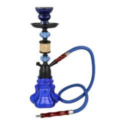 Vodní dýmka Woody blue 35cm-Vodní dýmka Woody Blue je vysoká 35 cm. Menší jednošlauchová vodní dýmka v modrém provedení má polotransparentní vázu ve tvaru květu. Vodní dýmka Woody je dodávaná s jedním proplachovatelým šlauchem s koženkovou omotávkou, který je ukončený nalisovaný dřevěným náustkem a konektorem pro připojení. Hadice se připojuje zasunutím do konektoru s použitím těsnění. Tělo do vázy se tradičně upevňuje nasunutím s použitím přiloženého gumového těsnění. Kovové tělo s ozdobnými prvky a talířek je v polomatné černé úpravě. Vodní dýmku Woody dodáváme v kartonové krabici.  V obsahu balení najdete: tělo dýmky, vázu, proplachovatelnou hadici s dřevěným náustkem a konektorem pro připojení, keramickou korunku, potřebné těsnění, talířek a kleště na uhlíky.  Celková výška vodní dýmky/vázy: 35 cm / 13,5 cm Výška/Horní vnitřní průměr korunky: 5,8 cm/ 5 cm Spodní vnitřní průměr korunky pro nasazení: 2 - 2,5 cm Horní vnější průměr korunky (pro nasazení badchy): 6 cm Délka hadice včetně náustku a konektoru: 100 cm Délka náustku: 13 cm Průměr připojovacího adaptéru na hadici: 1,2 cm  Průměr talířku: 9,8 cm