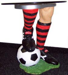 Stolek Fotbal-Stolek s kulatou deskou o průměru cca 50cm a opěrnou nohou v designu nohy hráče opřenou o míč. Výška cca 50-60cm.